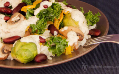 Colorful salad with rice, beans, vegetables and aromatic cashew sauce