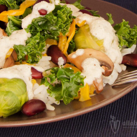 Colorful salad with rice, beans, vegetables and aromatic cashew sauce.