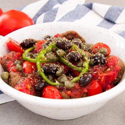 Greek, traditional cretan dakos salad. With rusks, tomatoes and olive oil. A vegan recipe.