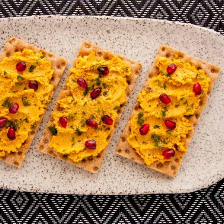 Photo of three crackers with vegan cashews cheese, substitute, spread and pomegranate seeds and dill as toping and a small bowl with the dip inside. A delicious vegan recipe!