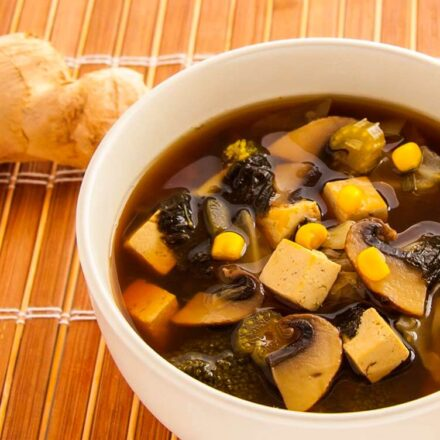 Photo of a tasty Chinese soup with veggies, fresh ginger, nori, tofu and mushrooms. A vegan recipe.