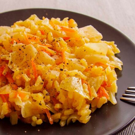 Photo of a plate with cabbage and rice risotto with a spoon at the side. A photograph part of the vegetarian and vegan recipe of delicious cabbage and rice risotto.
