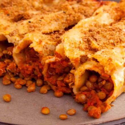 A photo of cooked cannelloni stuffed with lentils, vegetables and tomatoes with almond milk and tomatoe suace. A vegan recipe from All About Vegans.