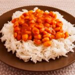 Photo of a plate with rice and chickpeas with red sauce on top. A vegan recipe of rice and chickpeas in curry and almond milk sauce called Chana Masala or Chole Masala).