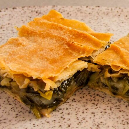 Photo of two pieces of Greek spinach, leeks and fennel pie. A vegetarian and vegan recipe.