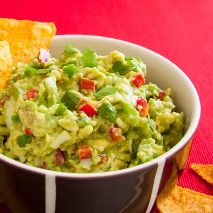 A photo of a Mexican guacamole dip served with nachos. A vegan recipe from All About vegans.
