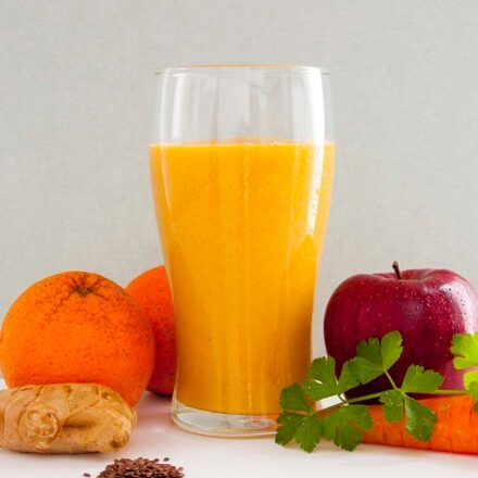A photo of a glass with an orange smoothie surrounded by oranges, apple, carrot, celery, ginger and flax seeds. A vegan recipe from All About Vegans.