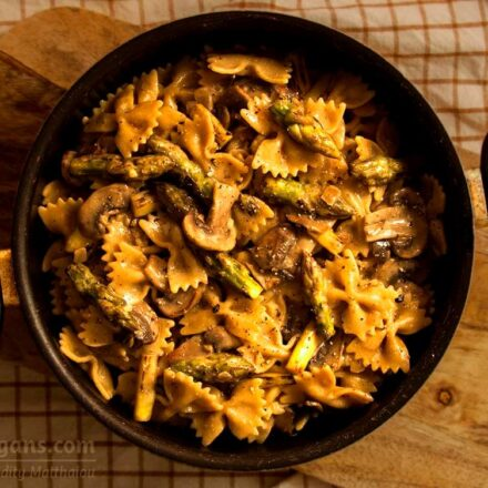 Photo of whole wheat pasta with asparagus and mushrooms in white sauce. A vegan recipe from All About Vegans.