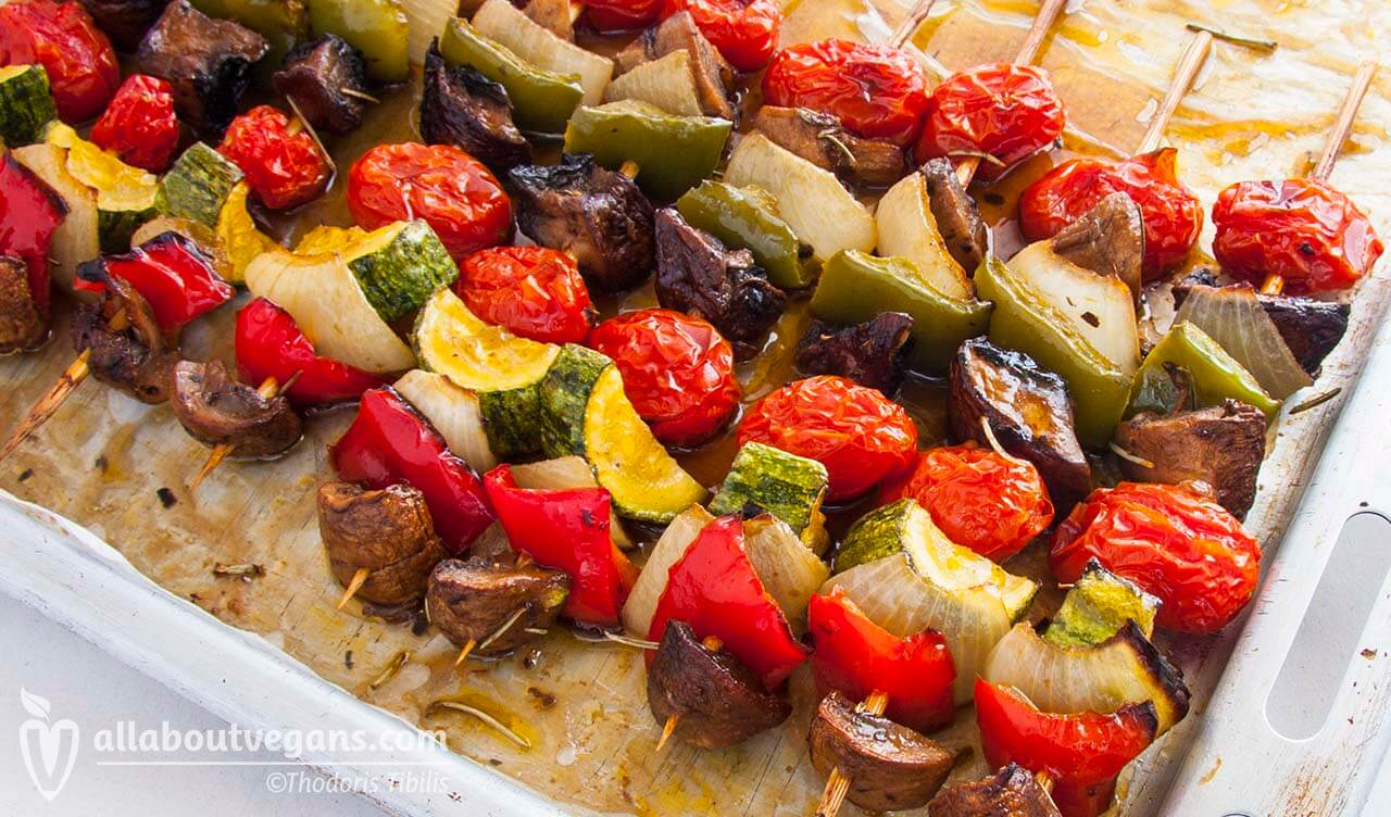 Photo of grilled vegetables skewers (souvlakia) with mushrooms, green and red peppers, cherry tomatoes and zucchini. A vegetarian and vegan recipe from All About Vegans.
