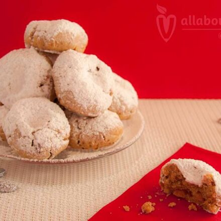 Photo with vegan Greek kourabiedes on a red Christmas background.