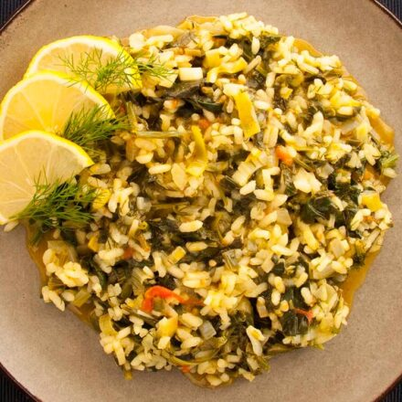 Photo of a plate with spinach with rice, leeks and tomato. A vegan & vegetarian version of the traditional Greek spanakorizo recipe.