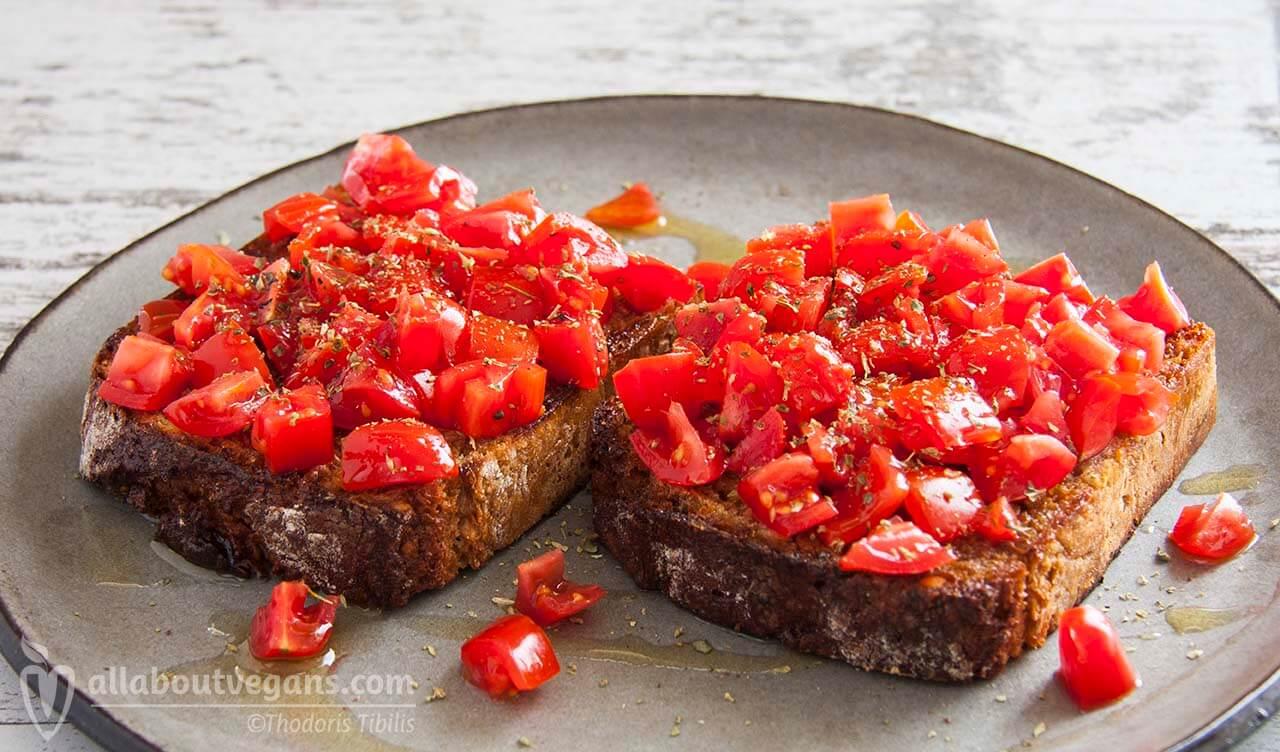 Φωτογραφία από δύο vegan μπρουσκέτες (φρυγανισμένες φέτες ψωμιού τριμμένες με σκόρδο) σερβιρισμένες με ντομάτα, σκόρδο, αλάτι, ρίγανη και ελαιόλαδο. Μία vegan συνταγή από το All About Vegans.