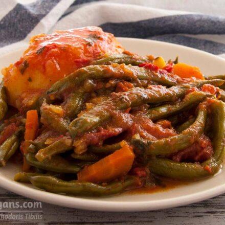 Φωτογραφία με ένα πιάτο με κοκκινιστά φρέσκα φασολάκια με λιαστές ντομάτες, πιπεριά Φλωρίνης και καρότα. Μία συνταγή βασισμένη στην παραδοσιακή ελληνική συνταγή, από το All About Vegans.