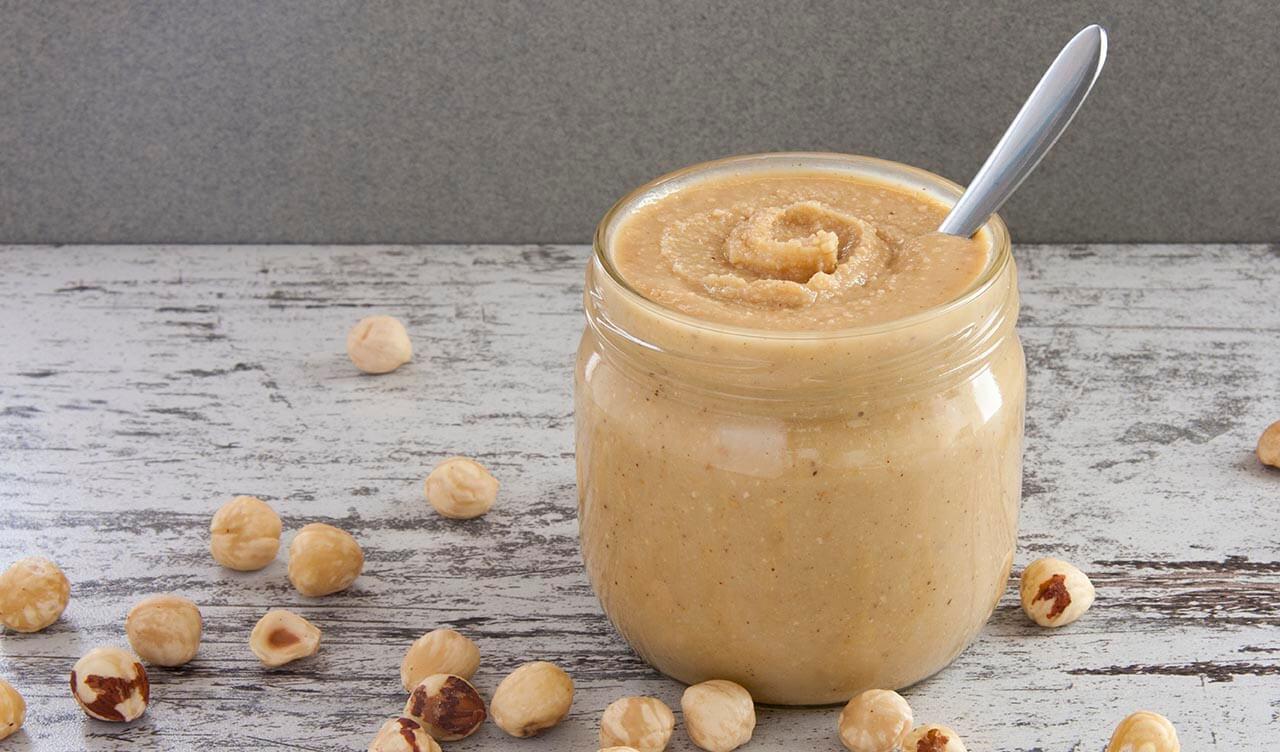 Φωτογραφία σπιτικού φουντουκοβούτυρου σε βάζο, περιτριγυρισμένο από φουντούκια. Μια βίγκαν και χορτοφαγική συνταγή από το All About Vegans.