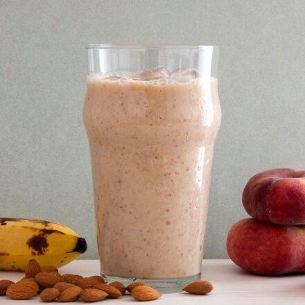Φωτογραφία ενός ποτηριού με smoothie περιτριγυρισμένου από πλακέ ροδάκινα (ούφο ή ντόνατ), μπανάνα και αμύγδαλα. Μία vegan και vegetarian συνταγή από το All About Vegans.