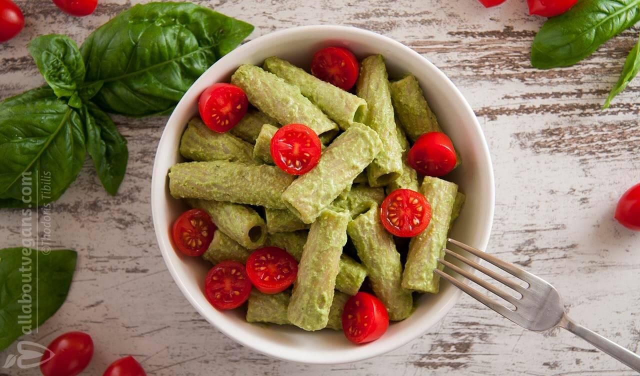 Φωτογραφία από ένα πιάτο ριγκατόνι με vegan πέστο και ντοματίνια. Διακόσμηση με φύλλα βασιλικού και ντοματίνια. Μία vegan συνταγή από το All About Vegans.