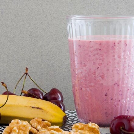 Photo of an intense vegan pink smoothie, surrounded by banana, cherries and walnuts. A vegan recipe from All About Vegans.